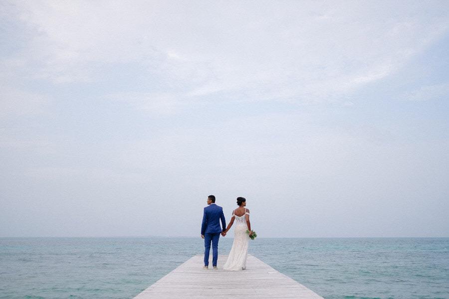 fotógrafo brasileiro destination wedding, foto de casal de mãos dadas de frente para o mar, em cancun