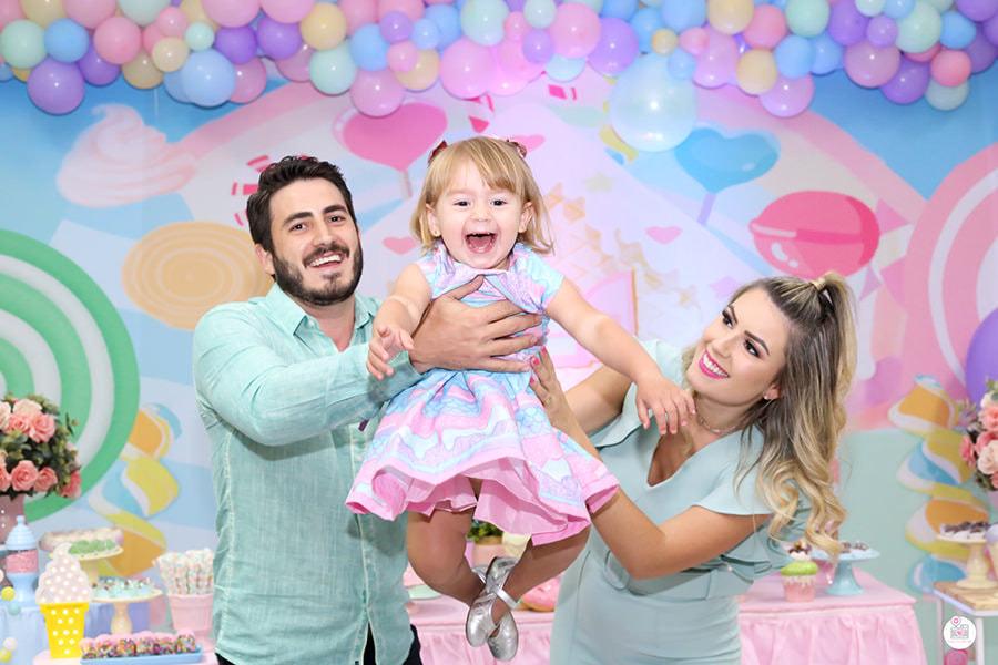 Aniversário infantil, pai e mãe na frente da decoração brincando com a filha, jogodo-a para cima e pegando-a em seu colo novamente comemorando o aniversário dela!