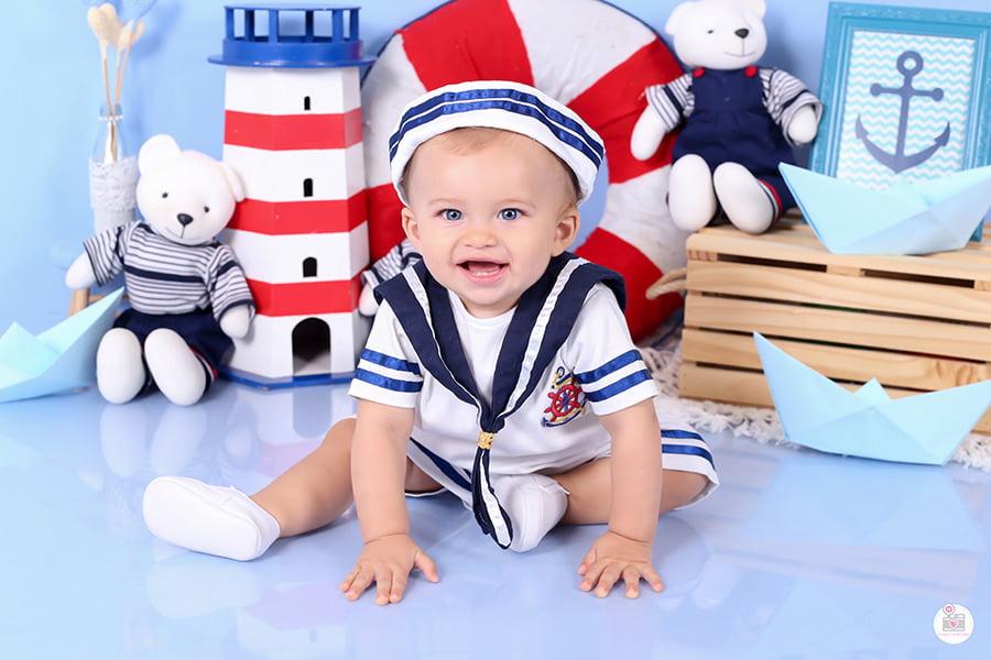 Ensaio fotográfico infantil em estúdio, de menino, com tema de marinheiro incluindo cenário personalizado nas cores e bebê com roupinha temática comemorando seu 8° mês de vida!