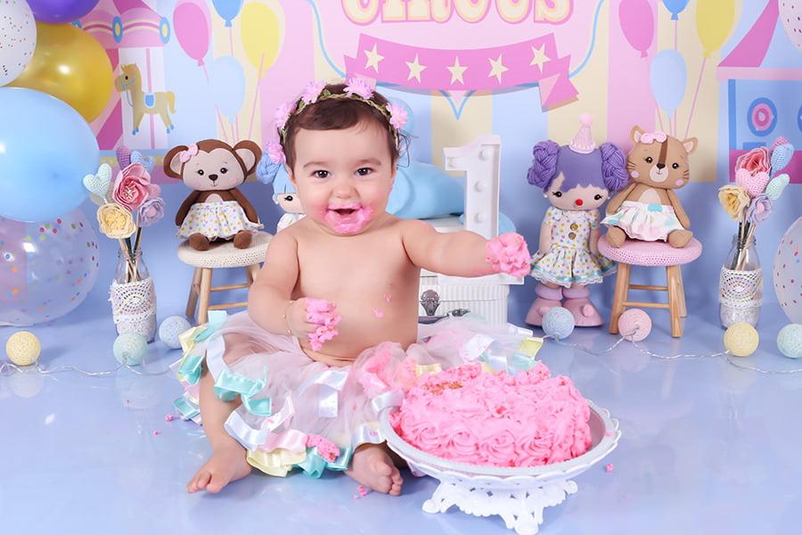 Ensaio fotográfico infantil em estúdio chamado smash the cake, (onde o bebê brinca com um bolo verdadeiro e se lambuza no decorrer das fotos. incluindo cenário com tema de circo, com cores suaves e delicadas para menina, com roupinha temárica para bebê comemorar seu 1° aninho de vida!