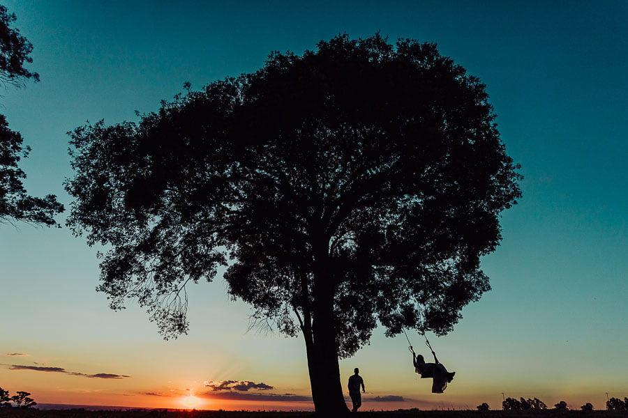 Silhueta de um casal no pôr-do-sol em um local bem aberto. A noiva está em um balanço e o noivo quem está balançando ela