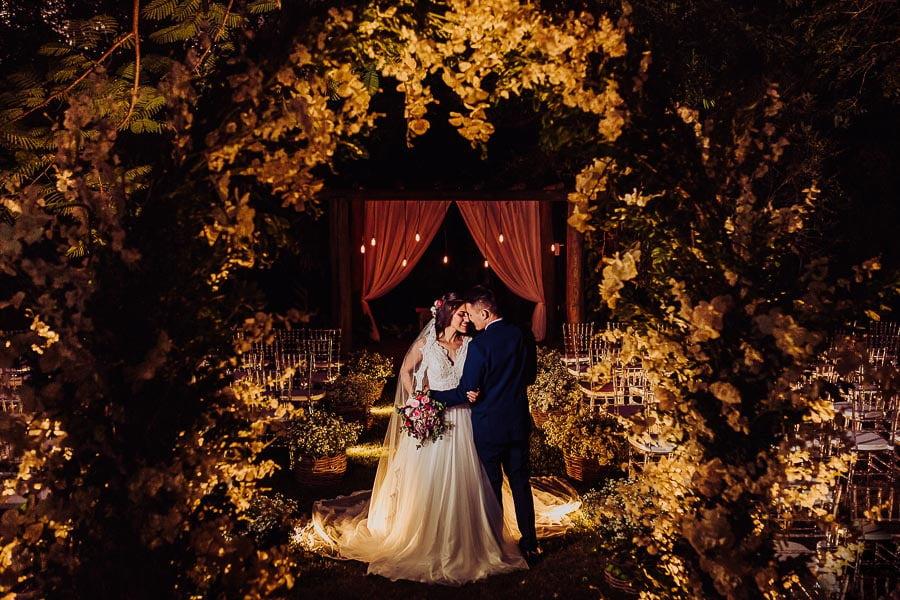 Casal de noivos no corredor da cerimônia, casamento ar livre, foto noturna.