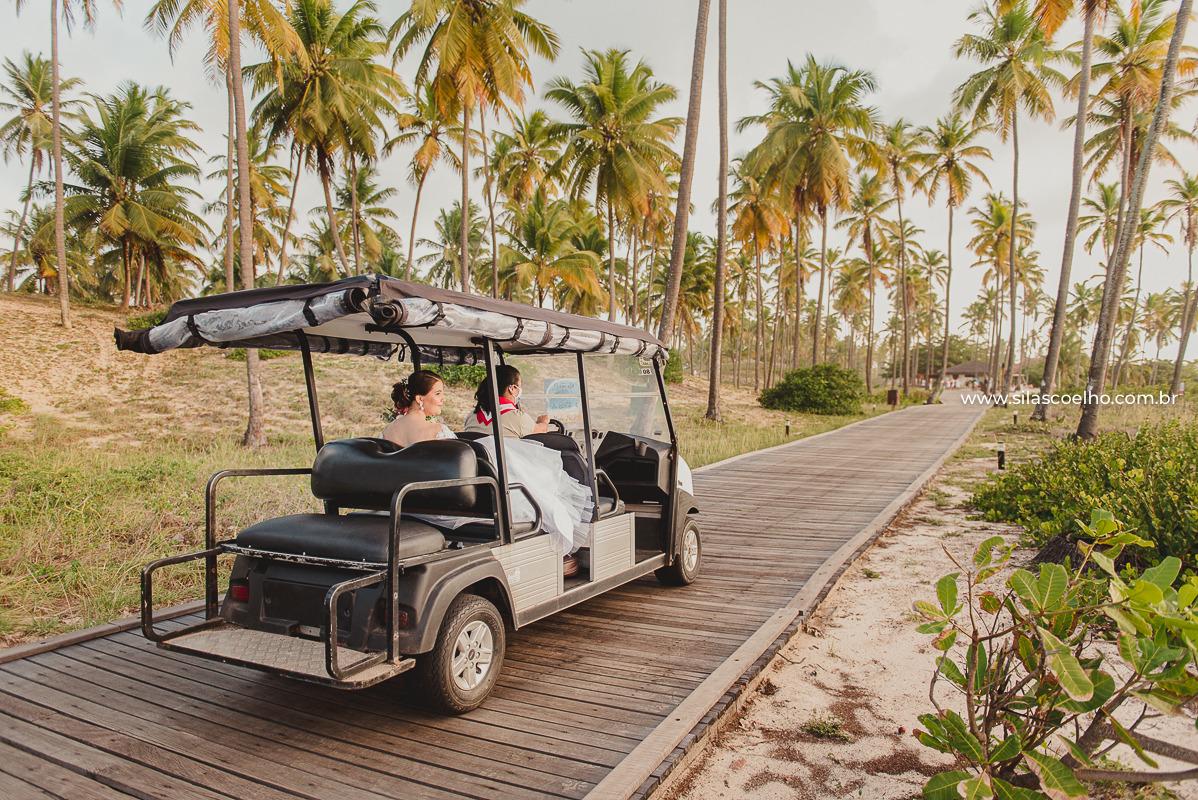 Noiva no carrinho de golfe indo para cerimônia de casamento, frente ao mar e no por do sol
