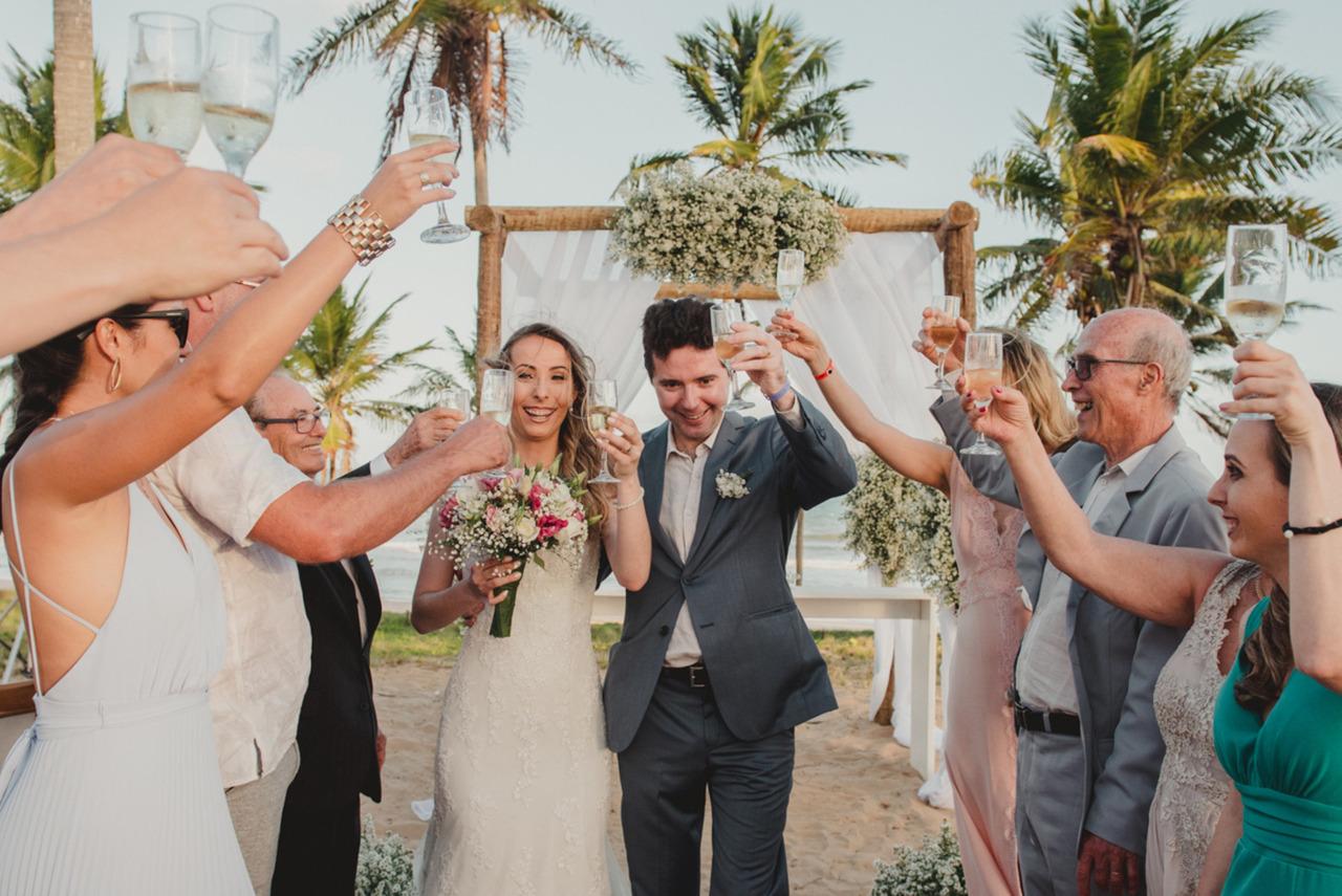 Noivos brindando seu destination wedding, frente ao mar e no por do sol com seus amigos e parentes