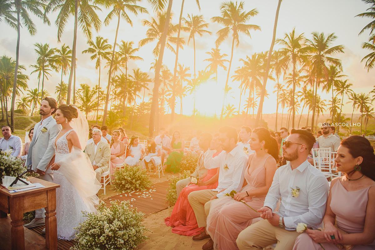 Noivos na ceriônia de casamento. Destination Wedding na praia e no pôr do sol