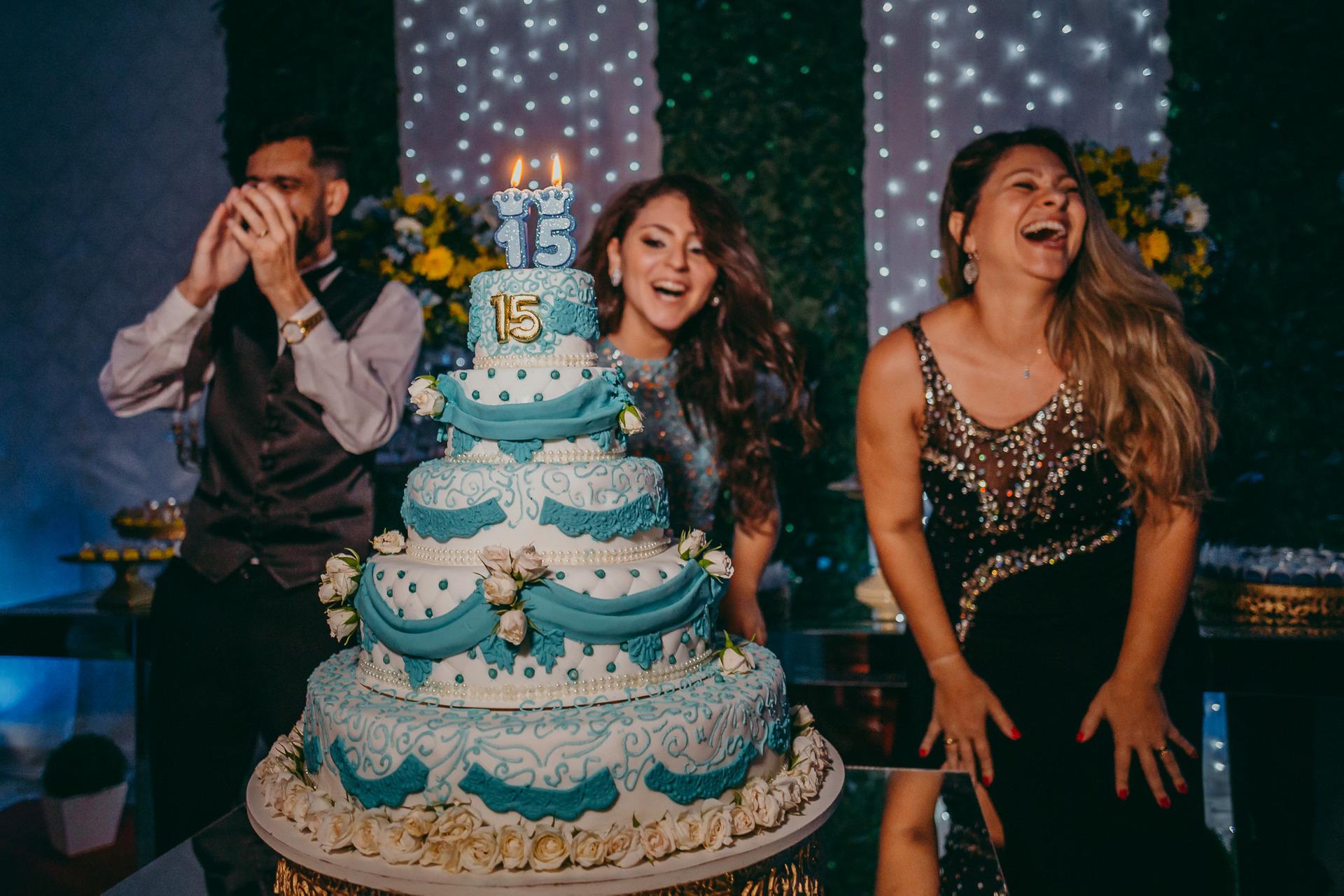 Foto de família sorrindo e muito animada atrás da mesa do bolo de 15 anos da aniversariante com tema azul