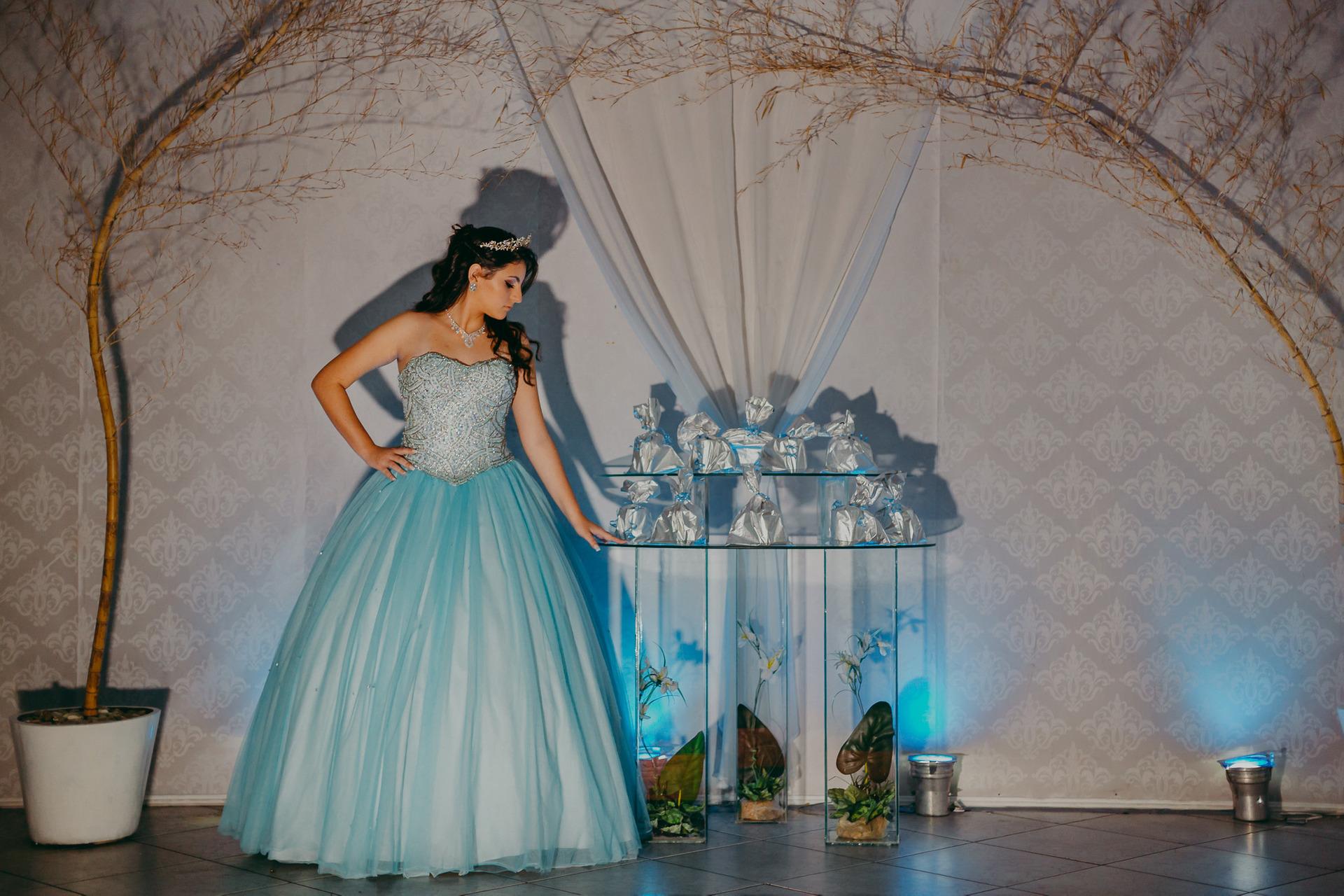 Fotografia de debutante com luz bem marcada em que olha para mesa de lembrancinhas numa pose elegante e com vestido azul fotos de 15 anos na SVM Festas  em Piedade no Rio de Janeiro