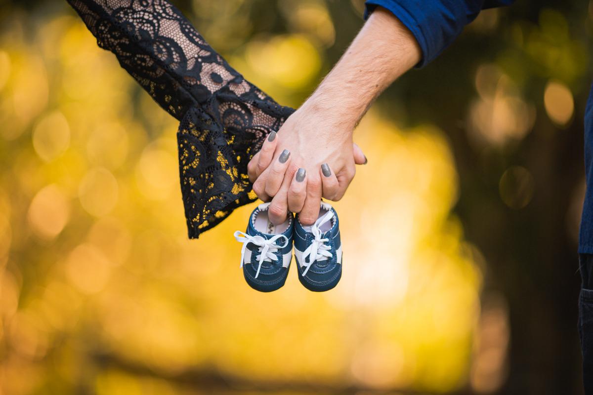 Casal segurando sapatinho de bebê na gravidez
