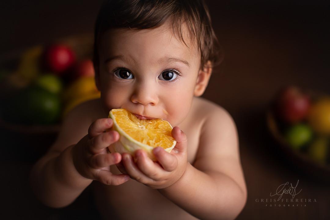 ensaio de bebe com fruta laranja