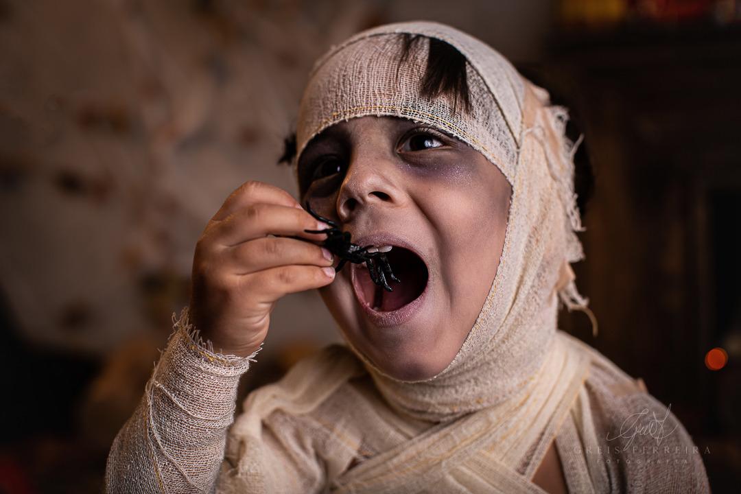 ensaio infantil de halloween mumia comendo aranha